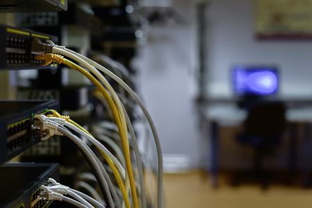 RJ45 cables plugged into switches in rack with work space on background Stock Photo