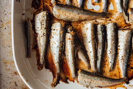 Roasted baltic herring on white plate. Oven tray on background Stock Photo