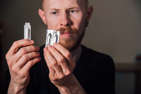 Sad young man holding suppository candle before using