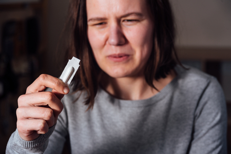 Young sad and sick woman holding suppository and wants using it Imagens