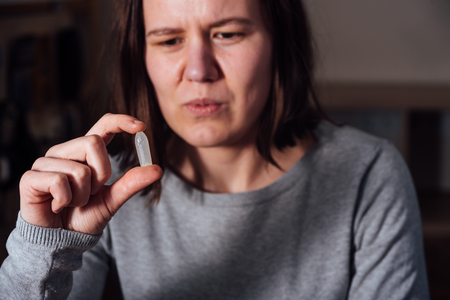 Young sad and sick woman holding suppository and wants using it Stock Photo
