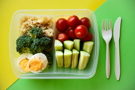 Lunch box with healthy food. Rice, broccoli, tomato, cucumber, eggs, apple and water. On yellow and green background