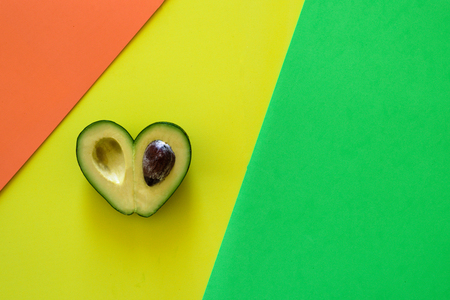 Heart-shaped slices of avocado on green, orange, yellow background