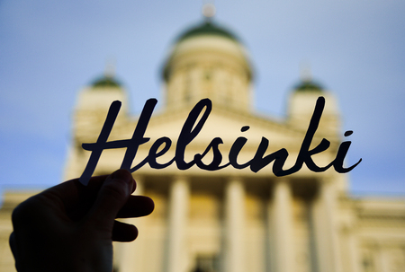 Word HELSINKI in hand with blurred Cathedral on background