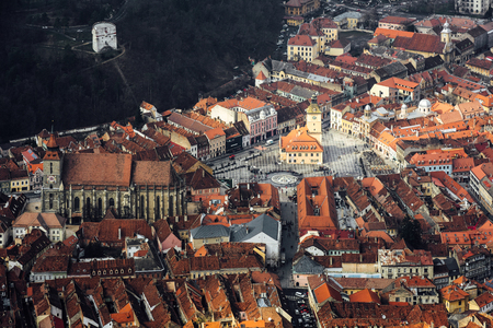 Great aerial view to Brasov old town. Town hall, Council square, Black church. A lot of red roofs buildings