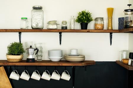 Plato y decoraciones en estantes de madera abiertos en la cocina blanca