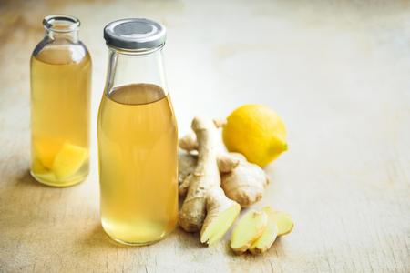 Bottle of detox ginger water on wooden background. Ingredients ginger, lemon, mint. Dieting concept.