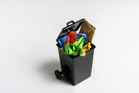 Trash bin with paper on grey background.