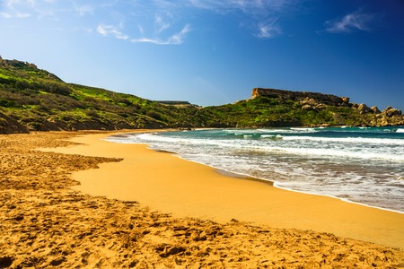 Malta Riviera beach, Mgarr. Ghajn Tuffieha Bay with golden sand. Mediterranean sea lagoon landscape Фото со стока