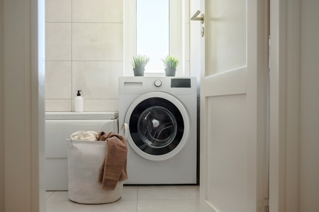 Washing machine in modern light bright bathroom. Laundry bag with towels near it. Scandinavian hygge style interior