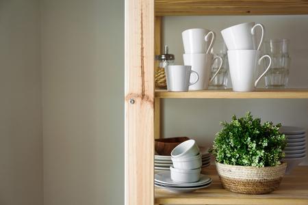 Geschirr und Dekorationen auf offenen Holzregalen in der weißen Küche