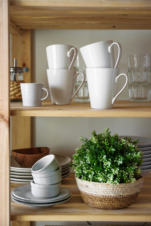 Dish and decorations on open wooden shelves in white kitchen