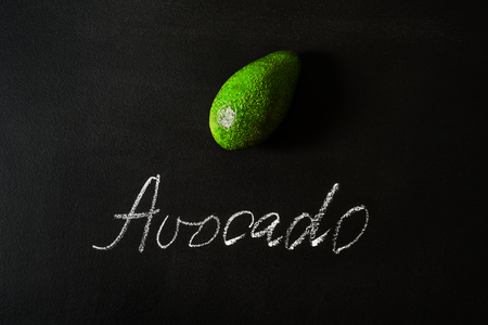 Avocado on black board with word Flat lay Imagens