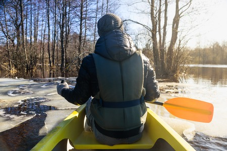 Man on canoe with paddle. Sailing in flooded spring forest at Soomaa, Estonia