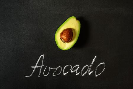 Avocado half on black board with word Flat lay