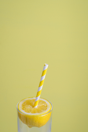 Lemon half with paper straw in glass on light yellow background. Summer, fresh and fun concept Imagens