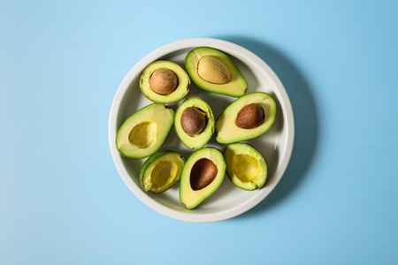 Avocado half on ceramic plate. Pastel light blue background. Text space