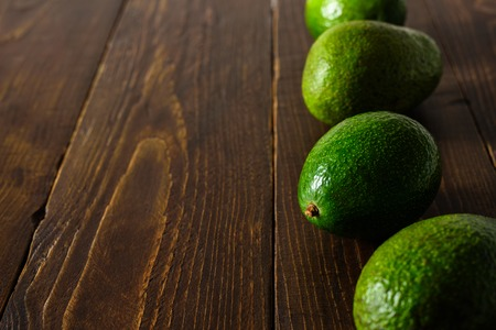 Avocados in row on dark wooden background. Text space