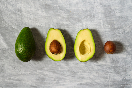 Avocado with half and seed on light grey background. Hard light