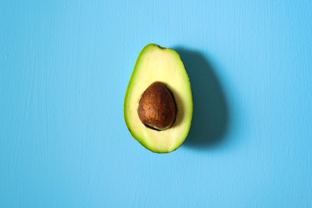 Avocado half on light blue background. Central conposition, hard light