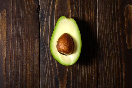 Avocado half on dark wooden background. Central conposition, hard light