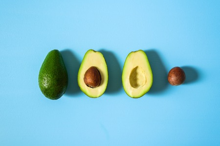 Avocado with half and seed on light blue background. Hard light Imagens