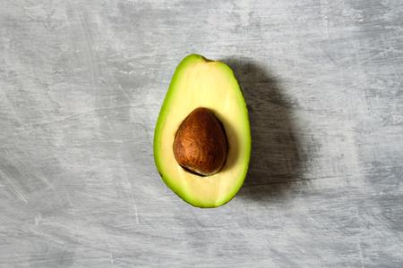 Avocado half on grey background. Central conposition, hard light Imagens
