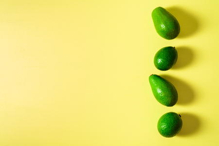 Avocados in row on pastel light yellow background. Hard liight. Text space Imagens