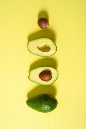 Avocado with half and seed on light yellow background. Hard light
