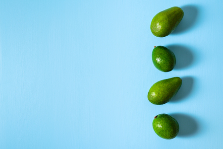 Avocados in row on pastel light blue background. Hard liight. Text space Imagens