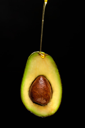 Avocado oil concept. Oil pouring on avocado. Oil drop on fruit. Black background, isolate