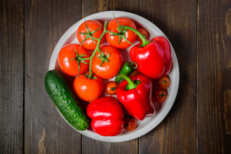 Juicy vibrant vegetables on ceramic plate. Tomato, cucumber, red bell pepper, jalapeno. Top view, flat lay