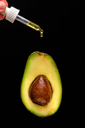 Avocado oil concept. Oil drop on pipette falling to avocado. Black background, isolate Imagens