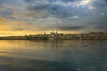 Classic postcard view to Basilica of Our Lady of Mount Carmel and St Pauls Pro-Cathedral. Valletta, Malta. Sky with moody clouds, sunrise