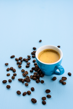 Blue espresso cup with coffee on blue pastel background with beans around