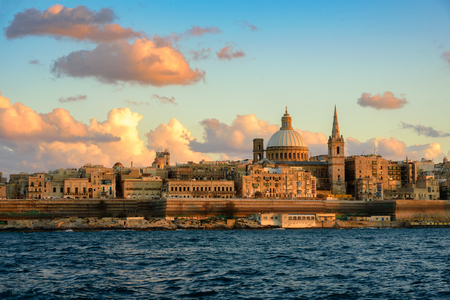 Classic postcard view to Basilica of Our Lady of Mount Carmel and St Pauls Pro-Cathedral. Valletta, Malta. Sky with beautiful clouds, pink sunset Imagens