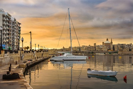 Classic postcard view to Basilica of Our Lady of Mount Carmel and St Pauls Pro-Cathedral. Valletta, Malta. Sky with moody clouds, sunrise. Yacht and boat on water
