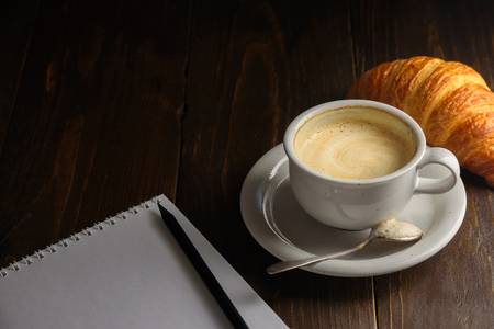 Cappuccino with croissant on dark wooden background. Text space. Blank notepad and pencil near it