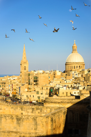Classic postcard view to Basilica of Our Lady of Mount Carmel and St Pauls Pro-Cathedral. Valletta, Malta. Clear sky, sunshine, flying birds