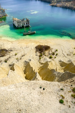 Abandoned quarry and prison Rummu, Estonia. View from sand hill to flooded quarry. Beach with blue water Imagens