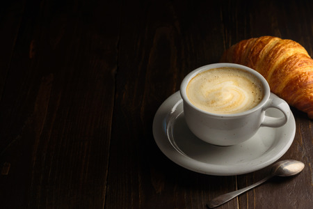 Cappuccino with croissant on dark wooden background. Text space
