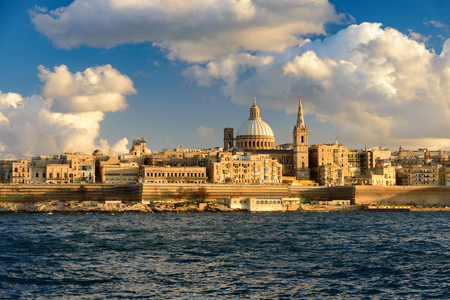 Classic postcard view to Basilica of Our Lady of Mount Carmel and St Pauls Pro-Cathedral. Valletta, Malta. Sky with beautiful clouds, sunshine Imagens