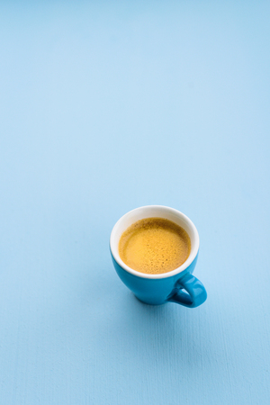 Blue espresso cup with coffee on blue pastel background