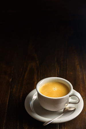 Black coffee on dark wooden background. Text space above the cup Imagens