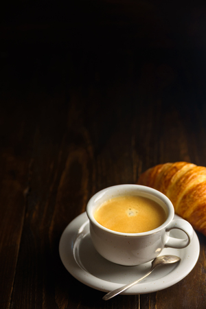 Black coffee with croissant on dark wooden background. Text space above the cup