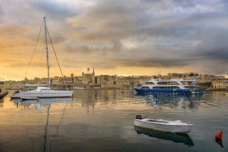 Classic postcard view to Basilica of Our Lady of Mount Carmel and St Pauls Pro-Cathedral. Valletta, Malta. Sky with moody clouds, sunrise. Yacht, cruise ferry and boat on water Imagens