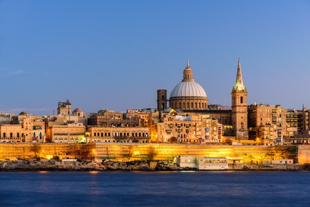 Classic postcard view to Basilica of Our Lady of Mount Carmel and St Pauls Pro-Cathedral. Valletta, Malta. Clear sky, sunset