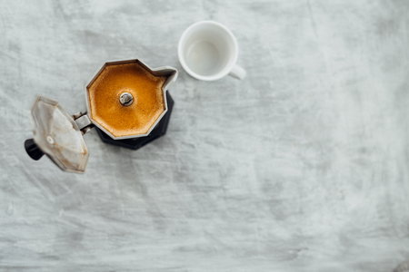 Moka pot with fresh brewed coffee and white cup on grey background Imagens
