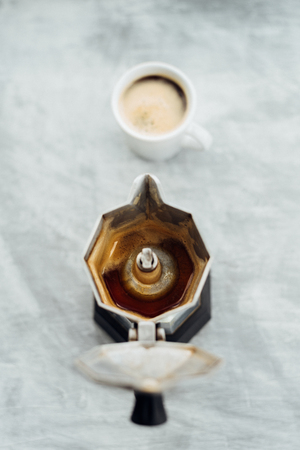 Empty moka pot with fresh brewed coffee and full cup on grey background