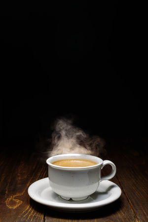 Hot coffee with steam in white ceramic cup on dark wooden backgound. Imagens